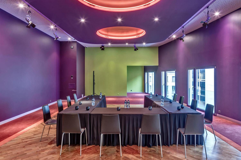 geräumiger Meeting Raum in Basel mit violetten Wänden und grauen Stühlen