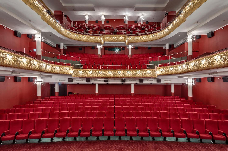 historischer Festsaal mit roten Samtsessel und Stühlen sowie golderer Deko