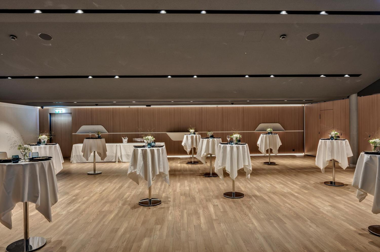 moderne Event Location mit hellem Holzboden weiss gedeckten Stehtischen und schönem Interieur