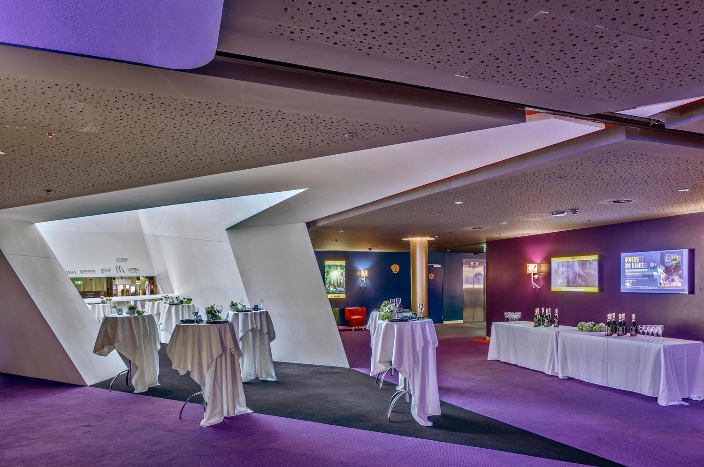skulpturale Event Fläche mit violletem Licht und weissen Tischdecken