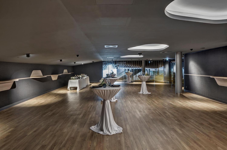moderne Event Location mit hellem Holzboden, grauen Wänden und weisser Decke
